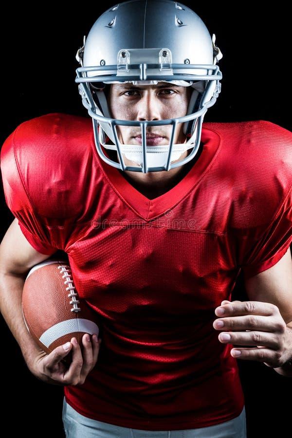 Ritratto di funzionamento sicuro del giocatore di football americano mentre tenendo palla fotografia stock libera da diritti