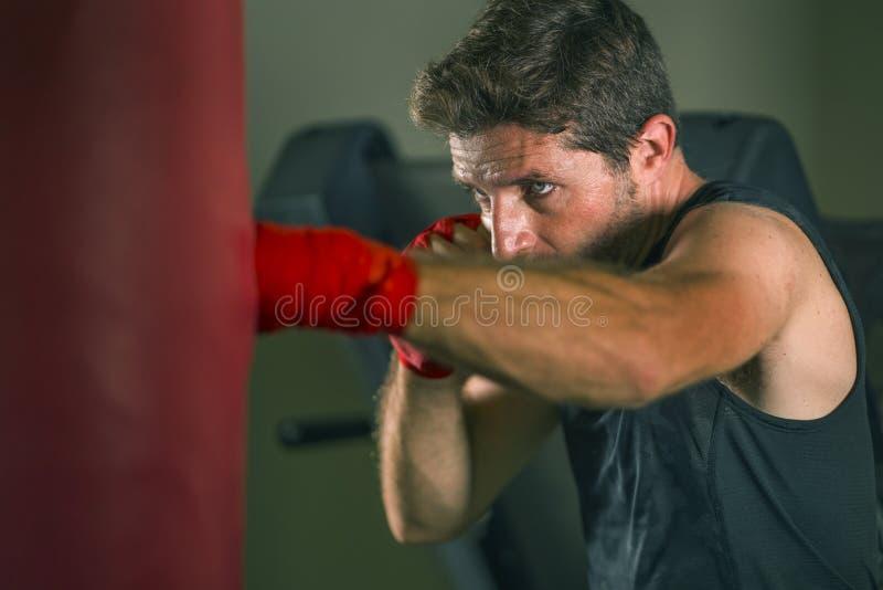 Ritratto di ginnastica di un giovane uomo attraente e dall'aspetto feroce che allena la boxe presso il palestra con un sacco di r immagine stock