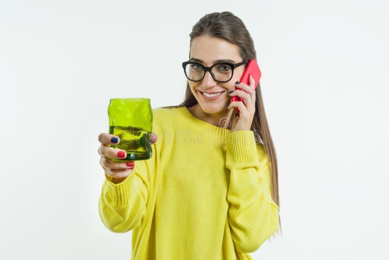 Ritratto di giovane acqua potabile sorridente della donna, succo da un vetro verde, parlando sul telefono, esaminante macchina fo fotografia stock