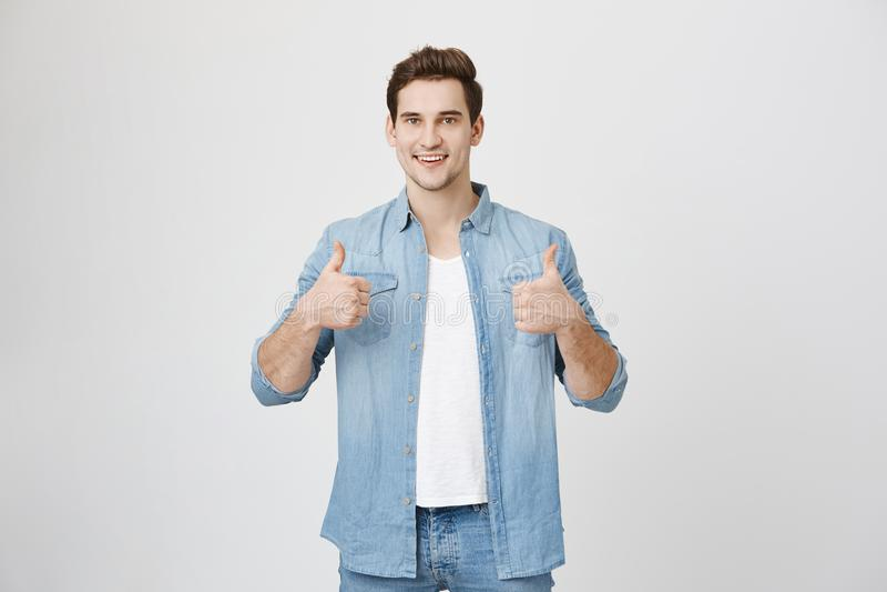 Ritratto di giovane adulto bello con l'espressione felice che tiene i suoi pollici su che mostrano approvement, isolato sopra bia immagine stock