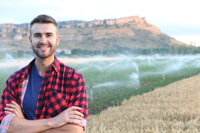 Ritratto di giovane agricoltore bello che sorride sul terreno coltivabile fotografia stock
