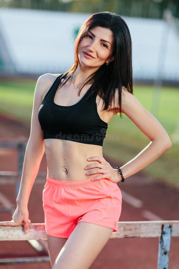 Ritratto di giovane atleta castana della donna sulla condizione sportiva di stile di vita dello stadio sulla pista che posa vicin fotografia stock libera da diritti