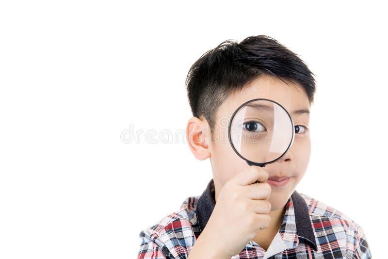 Ritratto di giovane bambino asiatico che guarda con un gla d'ingrandimento immagini stock