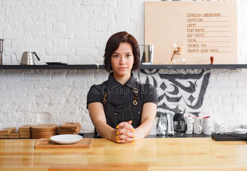 Ritratto di giovane barista al contatore della caffetteria fotografia stock