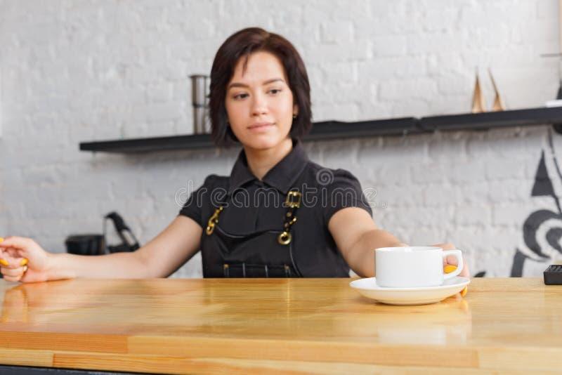 Ritratto di giovane barista al contatore della caffetteria fotografie stock