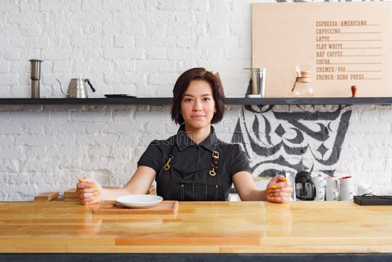 Ritratto di giovane barista al contatore della caffetteria fotografie stock libere da diritti