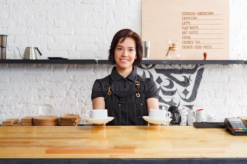 Ritratto di giovane barista al contatore della caffetteria fotografia stock libera da diritti
