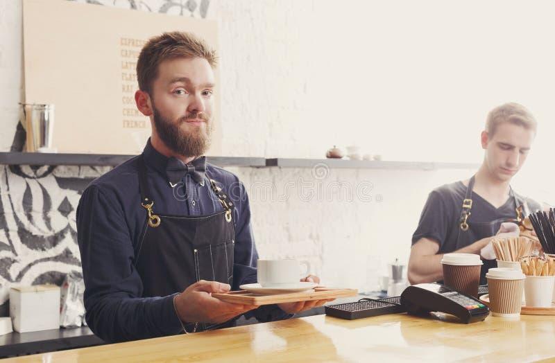 Ritratto di giovane barista al contatore della caffetteria immagini stock libere da diritti