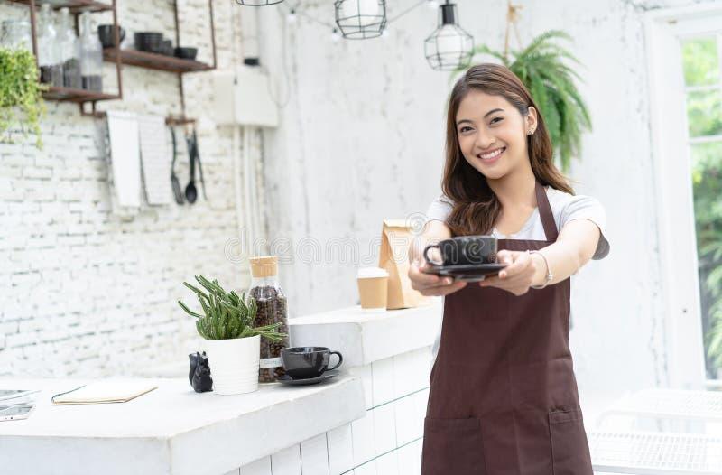 Ritratto di giovane barista asiatico sorridente in grembiule che sorride e che offre una tazza di caffè sopra accanto alla macchi fotografia stock libera da diritti