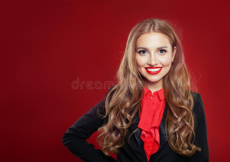 Ritratto di giovane bella donna di affari sicura in vestito Ragazza che sorride e che esamina macchina fotografica su fondo rosso fotografia stock