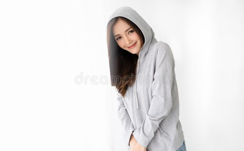 Ritratto di giovane bella donna asiatica in una condizione grigia di maglia con cappuccio vicino alla finestra che si rilassa e c immagini stock