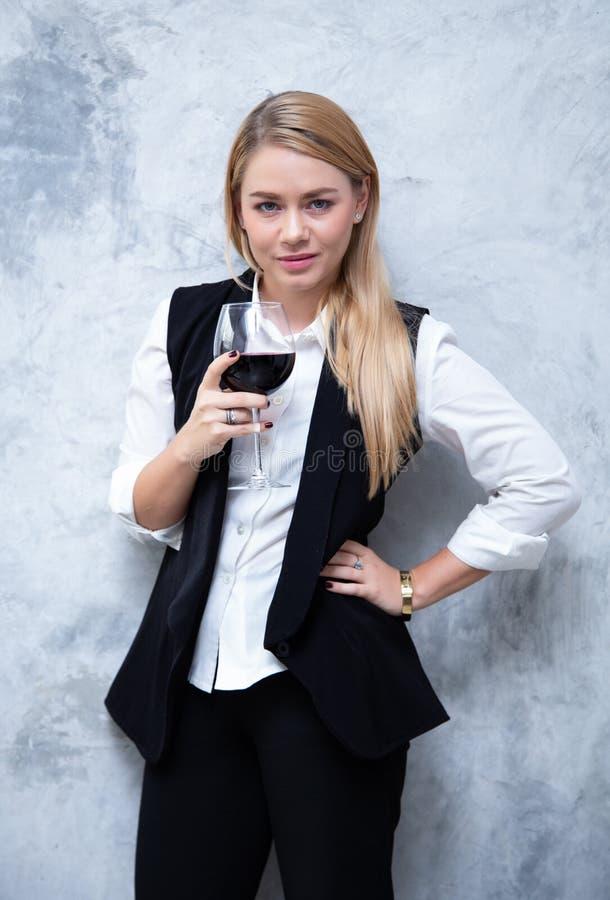 Ritratto di giovane bella donna attraente che tiene champagne e che esamina macchina fotografica sul fondo del muro di cemento de immagini stock libere da diritti