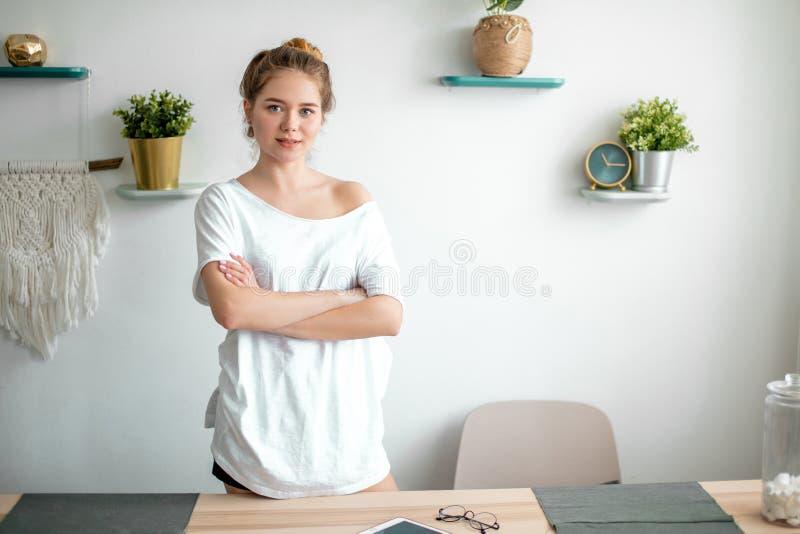Ritratto di giovane bella donna in attrezzatura casuale che sta con le armi attraversate immagini stock