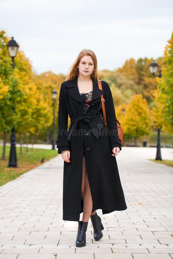 Ritratto di giovane bella donna in cappotto nero fotografie stock libere da diritti