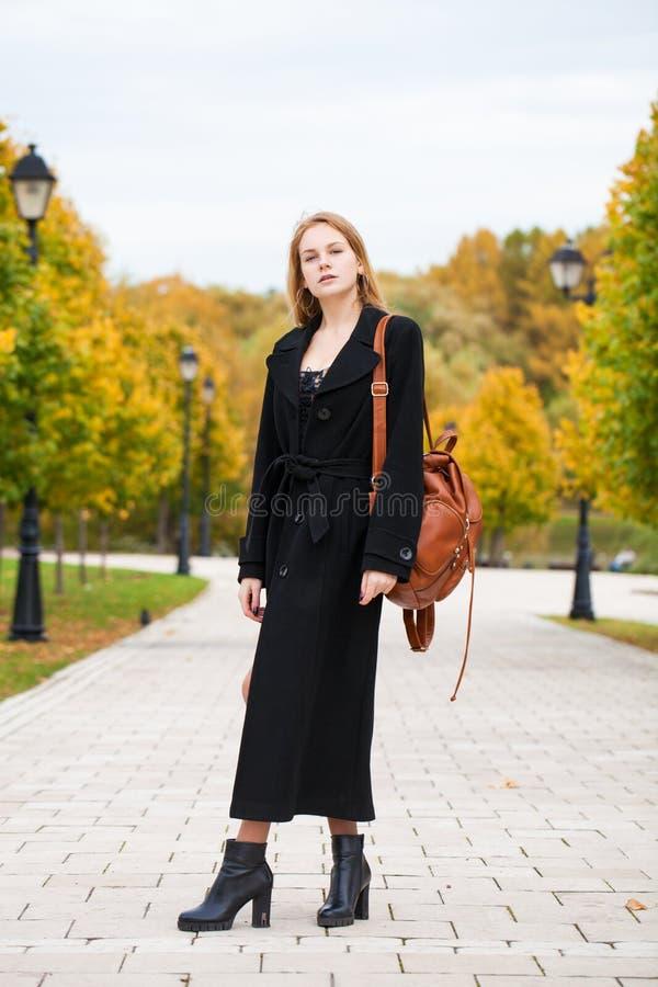 Ritratto di giovane bella donna in cappotto nero immagine stock