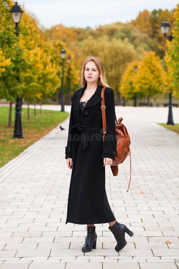 Ritratto di giovane bella donna in cappotto nero fotografia stock