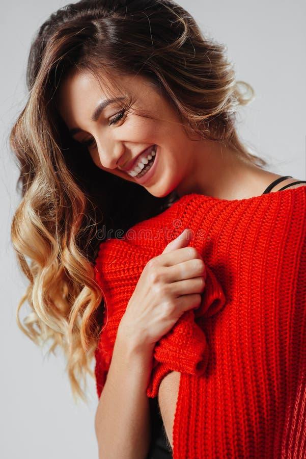Ritratto di giovane bella donna caucasica in maglietta rossa cheerfuly che sorride esaminando macchina fotografica immagine stock libera da diritti