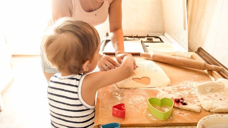 Ritratto di giovane bella donna che insegna al suo ragazzo del piccolo bambino che produce i biscotti e che cuoce le torte sulla  fotografie stock