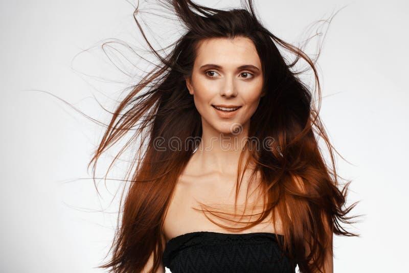 Ritratto di giovane bella donna con capelli che volano dal vento e dalle spalle nude Foto dello studio fotografia stock
