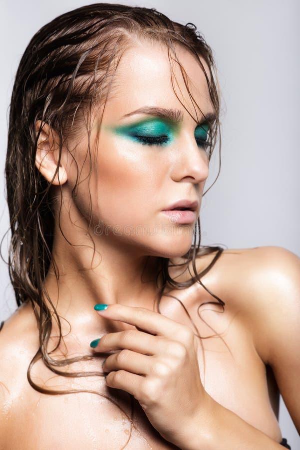 Ritratto di giovane bella donna con trucco brillante bagnato verde fotografia stock