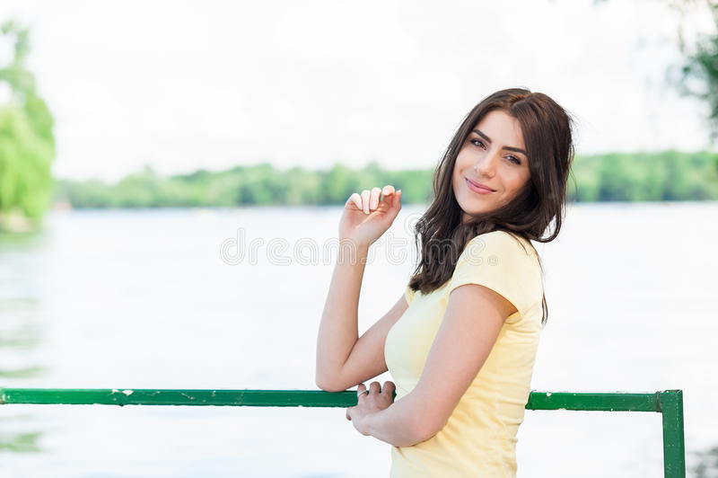 Ritratto di giovane bella donna contro il lago nel parco della città di estate immagine stock