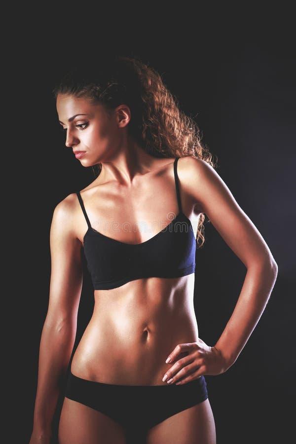 Ritratto di giovane bella donna di forma fisica, su fondo nero immagini stock libere da diritti