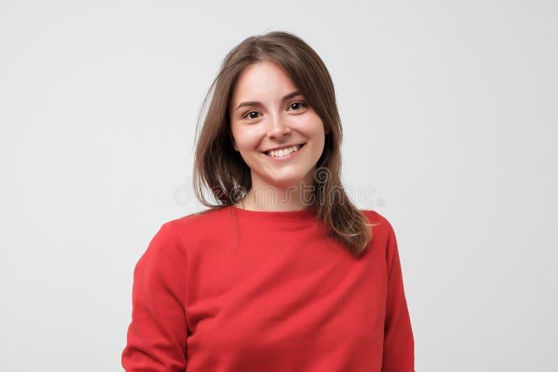 Ritratto di giovane bella donna gcaucasian in maglietta rossa cheerfuly che sorride esaminando macchina fotografica immagini stock libere da diritti
