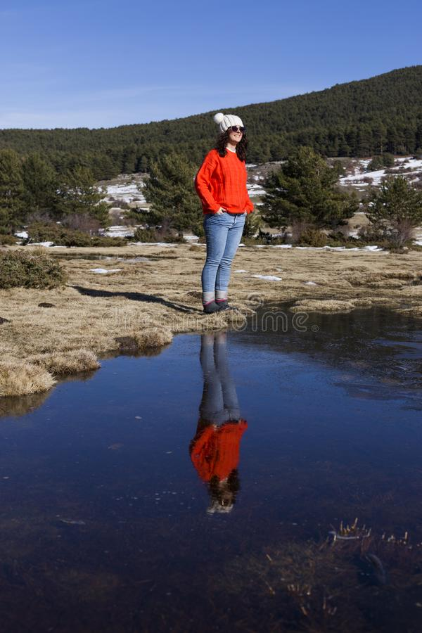 Ritratto di giovane bella donna nella montagna con la riflessione sull'acqua tempo soleggiato Vestiti caldi d'uso lifestyle fotografia stock