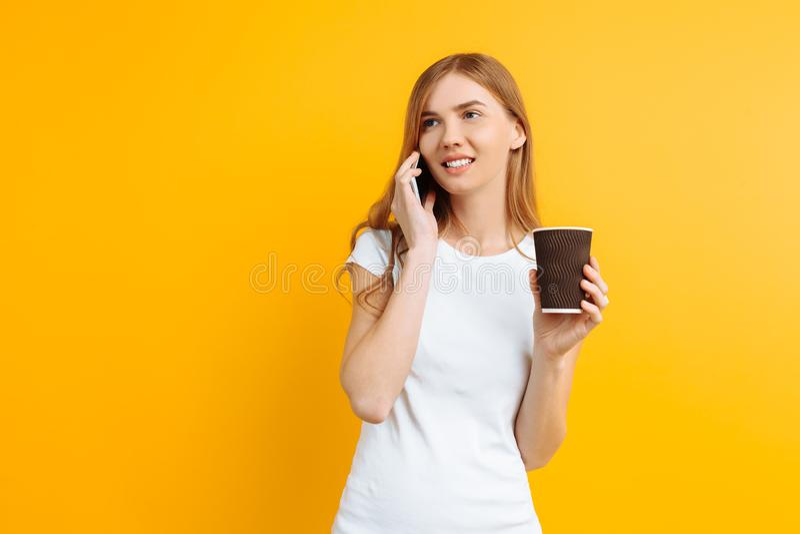 Ritratto di giovane bella donna, parlante sul telefono e tenente un vetro di caffè in sue mani, su un fondo giallo fotografie stock
