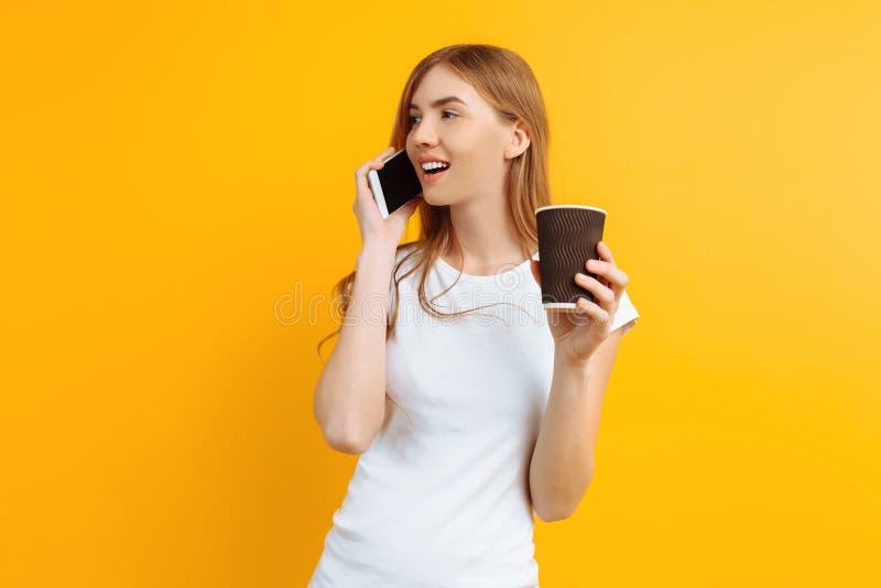 Ritratto di giovane bella donna, parlante sul telefono e tenente un vetro di caffè in sue mani, su un fondo giallo fotografia stock libera da diritti