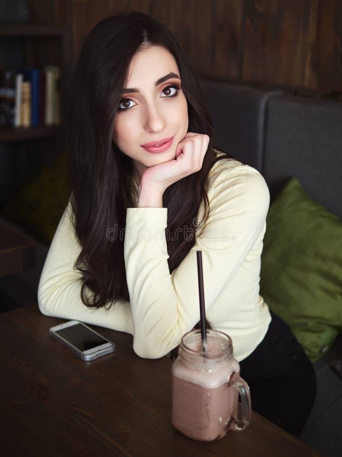 Ritratto di giovane bella donna premurosa sorridente che gode del tempo libero di fine settimana in film d'annata del caffè accog immagine stock