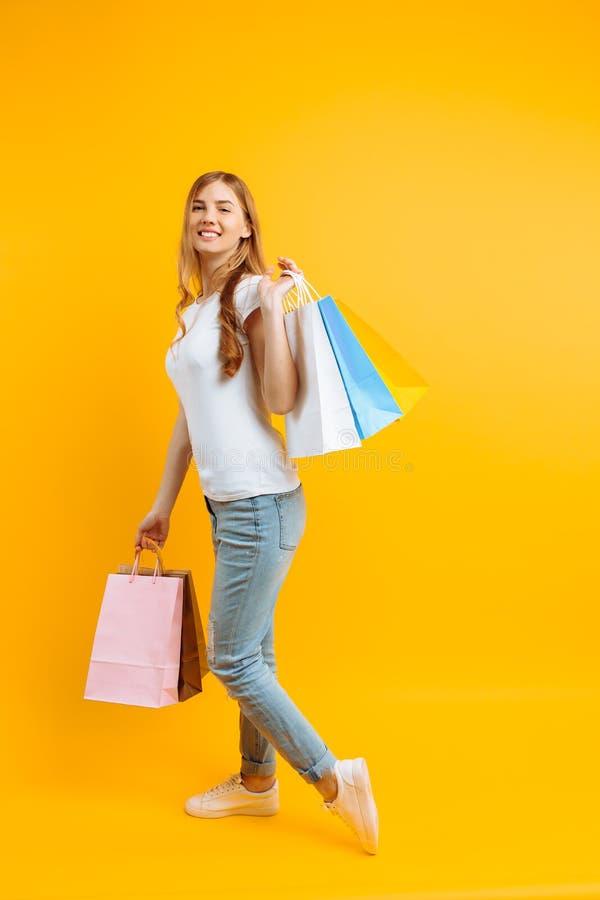 Ritratto di giovane bella donna in una maglietta bianca, con delle le borse colorate multi, su un fondo giallo immagine stock libera da diritti