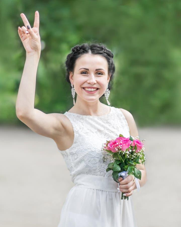 Ritratto di giovane bella femmina sorridente felice della sposa con il mazzo di nozze che mostra gesto del segno di V e che esami fotografia stock libera da diritti
