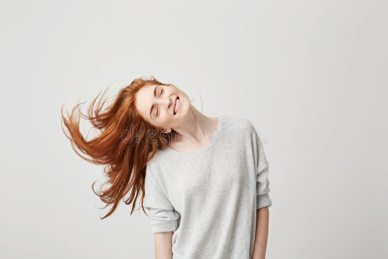 Ritratto di giovane bella ragazza allegra della testarossa che sorride con gli occhi chiusi che scuotono testa e capelli sopra fo fotografie stock