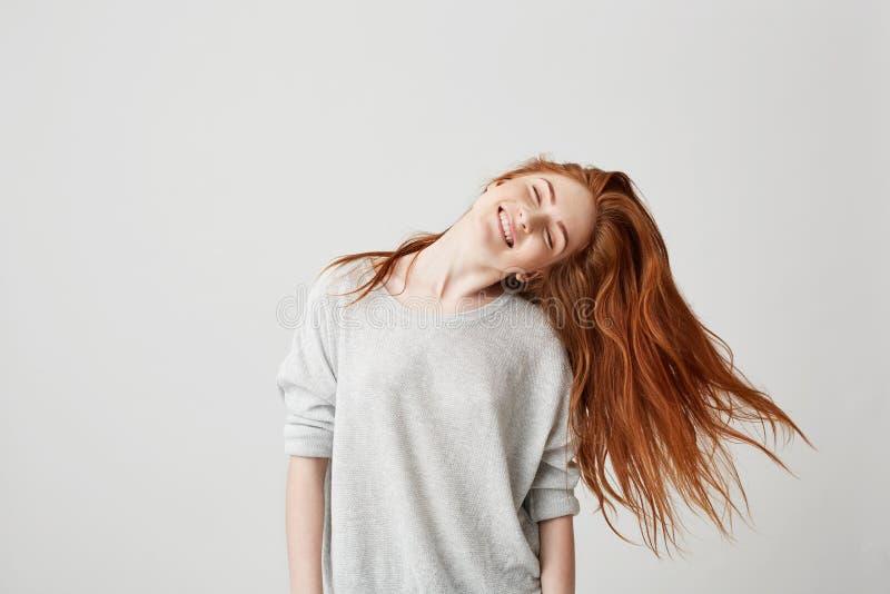 Ritratto di giovane bella ragazza allegra della testarossa che sorride con gli occhi chiusi che scuotono testa e capelli sopra fo fotografie stock libere da diritti
