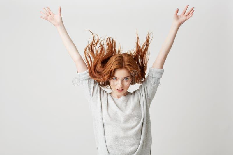Ritratto di giovane bella ragazza allegra della testarossa che sorride esaminando macchina fotografica che scuote capelli sopra f immagine stock libera da diritti