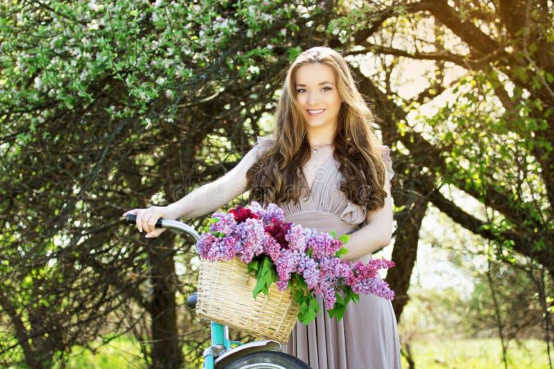 Ritratto di giovane bella ragazza con capelli lunghi in vestito luminoso con la merce nel carrello dei fiori sulla bici d'annata  fotografie stock
