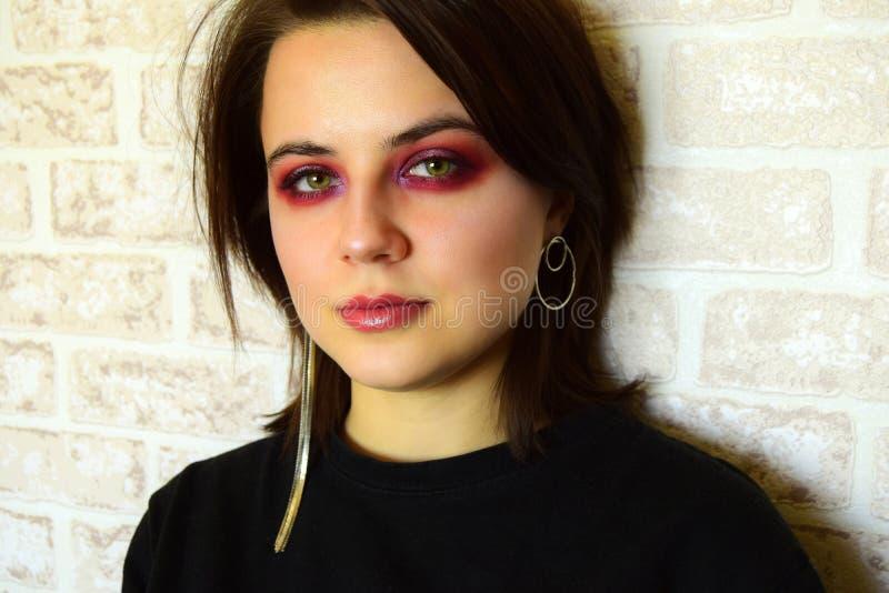 Ritratto di giovane bella ragazza con gli occhi verdi e un trucco creativo luminoso nei toni lilla fotografia stock