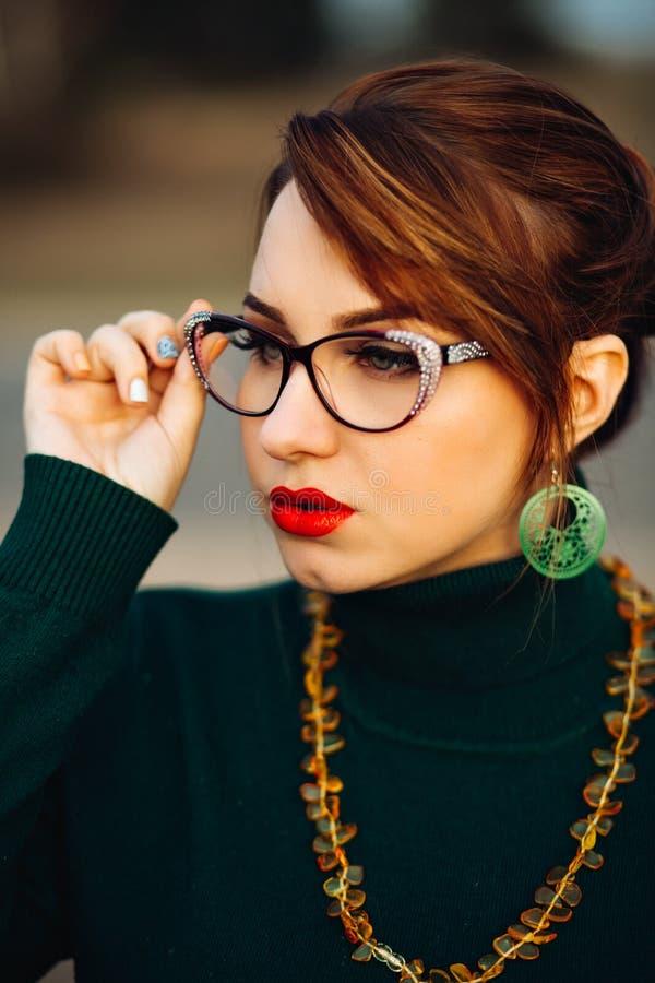 Ritratto di giovane bella ragazza con i vetri per visione Bello trucco luminoso, occhi verdi, labbra grassottelle rosse Verde fotografia stock