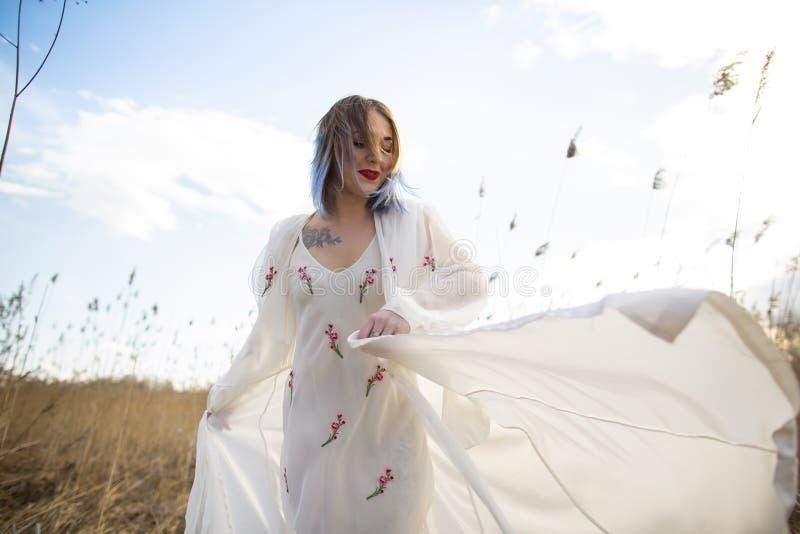 Ritratto di giovane bella ragazza nel vestito bianco nel giacimento di grano, camminare, spensierata Godere di bello giorno soleg fotografie stock libere da diritti