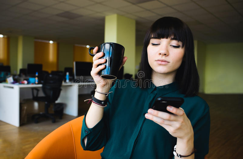 Ritratto di giovane bello impiegato di concetto femminile che usa un telefono cellulare e la tenuta della tazza della bevanda fotografie stock