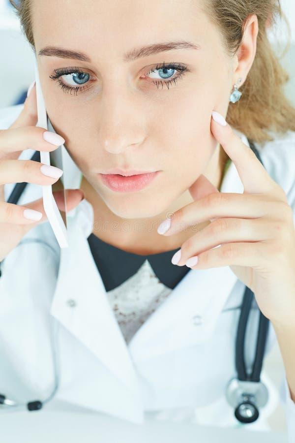 Ritratto di giovane bello medico che parla sul telefono fotografia stock