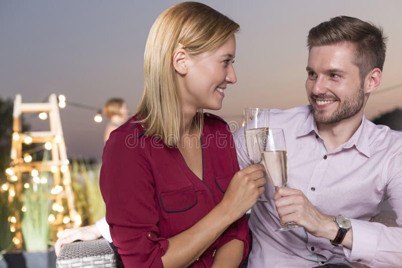 Ritratto di giovane bicchiere di vino sorridente della tenuta della donna di affari mentre stando contro i colleghi al tetto dura fotografia stock