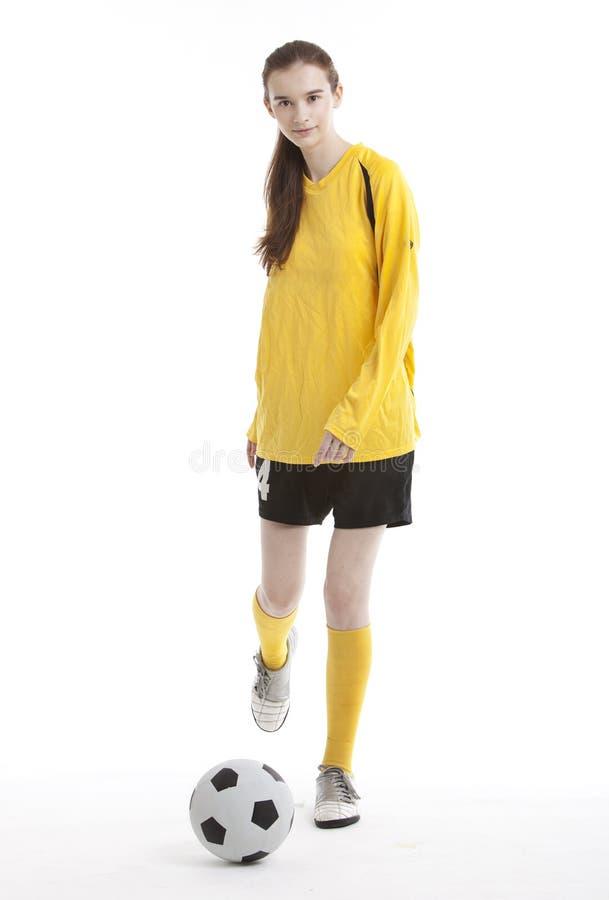 Ritratto di giovane calciatore femminile che dà dei calci alla palla contro il fondo bianco fotografie stock