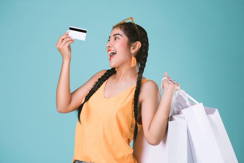 Ritratto di giovane carta di credito e dei sacchetti della spesa castana allegra della tenuta della donna fotografia stock libera da diritti