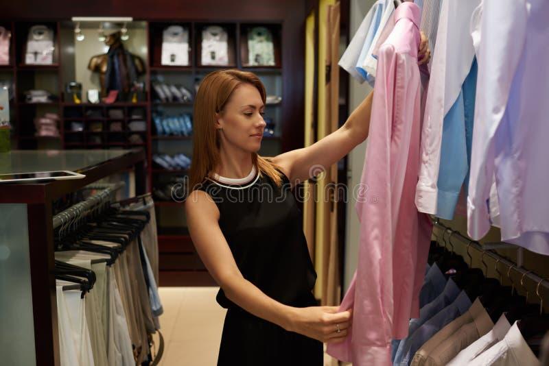 Ritratto di giovane cliente attraente della donna che tiene camicia alla moda per gli uomini mentre stando nel deposito di marca immagine stock libera da diritti