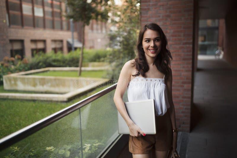 Ritratto di giovane computer portatile sorridente della tenuta della donna fotografia stock libera da diritti