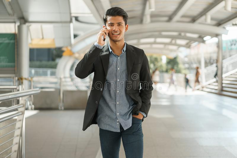 Ritratto di giovane condizione dell'uomo d'affari all'ufficio esterno e di conversazione sullo smartphone Vestito di usura di uom fotografia stock
