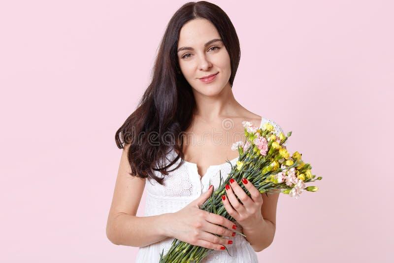 Ritratto di giovane condizione di modello sincera sorridente isolato sopra fondo rosa-chiaro, tenente i fiori colourful della mol immagini stock