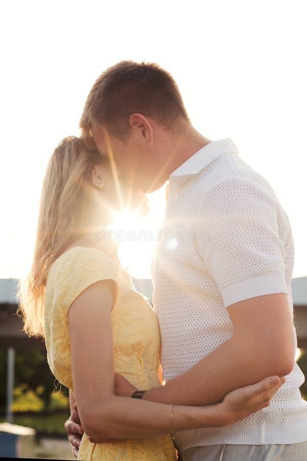 Ritratto di giovane coppia della famiglia che abbraccia baciare nelle macchie di luce solare immagini stock